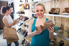 Girl showing a chosen pair of shoes. Young blond girl showing a chosen pair of shoes while her friend still choosing royalty free stock images