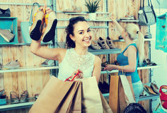 girl showing a chosen pair of shoes. Young cheerful girl showing a chosen pair of casual shoes while her friend still choosing royalty free stock photography