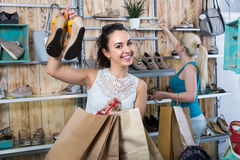 girl showing a chosen pair of shoes. Young cheerful girl showing a chosen pair of casual shoes while her friend still choosing stock images