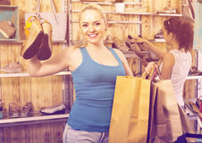 girl showing a chosen pair of shoes. Young cheerful girl showing a chosen pair of shoes while her friend still picking stock photography