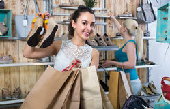 girl showing a chosen pair of shoes. Young cheerful girl showing a chosen pair of shoes while her friend still selecting stock photos