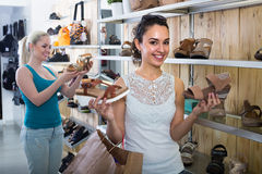 girl showing a chosen pair of shoes. Young cheerful girl 25s showing a chosen pair of shoes while her friend still choosing stock images