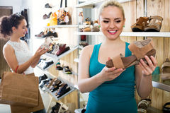 girl showing a chosen pair of shoes. Young cheerful girl 25s showing a chosen pair of shoes while her friend still choosing royalty free stock photo