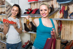 Girl showing a chosen pair of shoes. Young cheerful girl showing a chosen pair of shoes while her friend buying royalty free stock photo