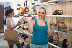 Girl showing a chosen pair of shoes. Young cheerful girl showing a chosen pair of shoes while her friend still choosing indoors stock photography