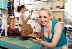 Girl showing a chosen pair of shoes. Young cheerful girl showing a chosen pair of shoes while her friend still shopping royalty free stock photo