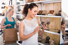 girl showing a chosen pair of shoes. Young girl showing a chosen pair of shoes while her friend still choosing royalty free stock photos