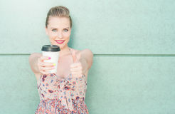 Girl showing coffee mug and making like gesture Royalty Free Stock Images