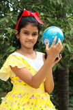 Girl showing the country. A small Indian girl showing a country on her educational globe Stock Photo