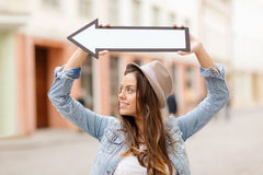 Girl showing direction with arrow in the city Royalty Free Stock Images