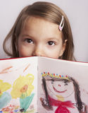 Girl showing drawings. Portrait of cute girl showing pictures in drawing book, studio background stock images