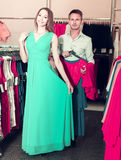 Girl is showing dress to male which waiting with new part of dre Royalty Free Stock Image