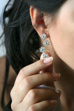 Girl showing the earring in the ear. The girl showing the earring in the ear Royalty Free Stock Images