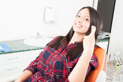 Girl showing fingers crossed sitting in dentist chair Royalty Free Stock Photos