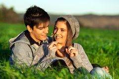 Girl showing flower to boyfriend outdoors. Stock Photography