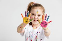 A girl showing her colorful painted hands. With smiley faces. Creative activity Stock Photography