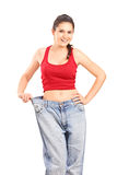 Girl showing her old, oversized pair of jeans Royalty Free Stock Photo