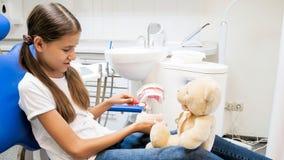 Teenage girl showing her teddy bear how to properly clean teeth. Girl showing her teddy bear how to properly clean teeth stock photo