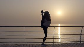 Girl showing incredible flexibility of the body. She stretches her legs while standing on the promenade near the sea. Morning sun. Bends into an arch standing stock footage