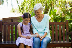 Girl showing mobile phone to grandmother while sitting on wooden bench Royalty Free Stock Images