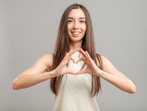 Girl showing OK sign. Young cute smiling girl showing OK sign  on gray backgroung Royalty Free Stock Photos