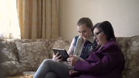 Girl showing old woman  tablet, using it on the window and wall background stock footage