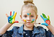 Girl showing painted hands. Little pretty girl showing painted hands and holding brush in mouth stock image