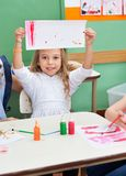 Girl Showing Painting At Classroom Desk Royalty Free Stock Photos