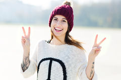 Girl showing peace sign. Attractive young woman outdoors, smiling Royalty Free Stock Photography