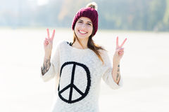 Girl showing peace sign. Attractive young woman outdoors, smiling Stock Photos