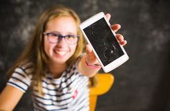 Girl showing a phone with broken screen. And smiling royalty free stock image