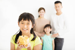 Girl showing the piggy bank and family finance concept Royalty Free Stock Photography