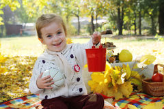 Girl showing red busket under autumn trees Royalty Free Stock Images