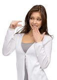 Girl showing small amount of something. Half-length portrait of woman showing small amount of something and covering mouth with a hand, isolated on white stock images