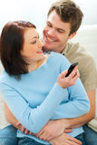 Girl showing something in mobile to boyfriend Stock Photos