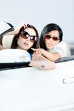 Girl showing something out of the auto. To her driving friend Royalty Free Stock Photo