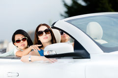 Girl showing something out of the convertible car Stock Photos