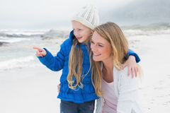 Girl showing something to mother at beach. Cute young girl showing something to smiling mother at the beach Royalty Free Stock Photos