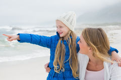 Girl showing something to mother at beach. Cute young girl showing something to smiling mother at the beach Royalty Free Stock Image