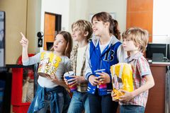 Girl Showing Something To Siblings At Cinema. Cute girl showing something to siblings with snacks at cinema Stock Photography