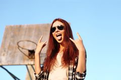 Girl showing symbol of rock music. In urban background Stock Image