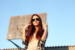 Girl showing symbol of rock music. In urban background Royalty Free Stock Photography