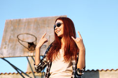 Girl showing symbol of rock music. In urban street scene Royalty Free Stock Images