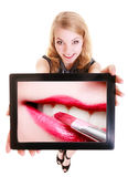 Girl showing tablet with lips lipstick. Makeup. Happy blond girl showing ipad with photo of female lips and red pink lipstick. Modern young woman holding tablet Stock Photos