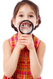 Girl showing teeth through a magnifier Royalty Free Stock Images