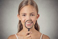 Girl showing teeth through a magnifying glass Royalty Free Stock Images