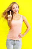 Girl showing a thumbs up. Portrait of attractive girl showing a thumbs up on yellow background Royalty Free Stock Photo