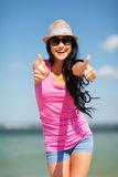 Girl showing thumbs up on the beach Royalty Free Stock Photo