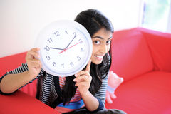 Girl showing time in a clock Stock Photography