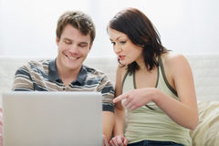 Girl showing to boyfriend something in laptop Stock Image